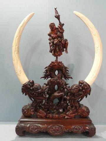 Sculpture en bois figurant un personnage dans sur deux dragons de part et d' autre deux défenses d' éléphant sculptées de grenouille, insectes, serpent et poissons - Vietnam, XIXème siècle