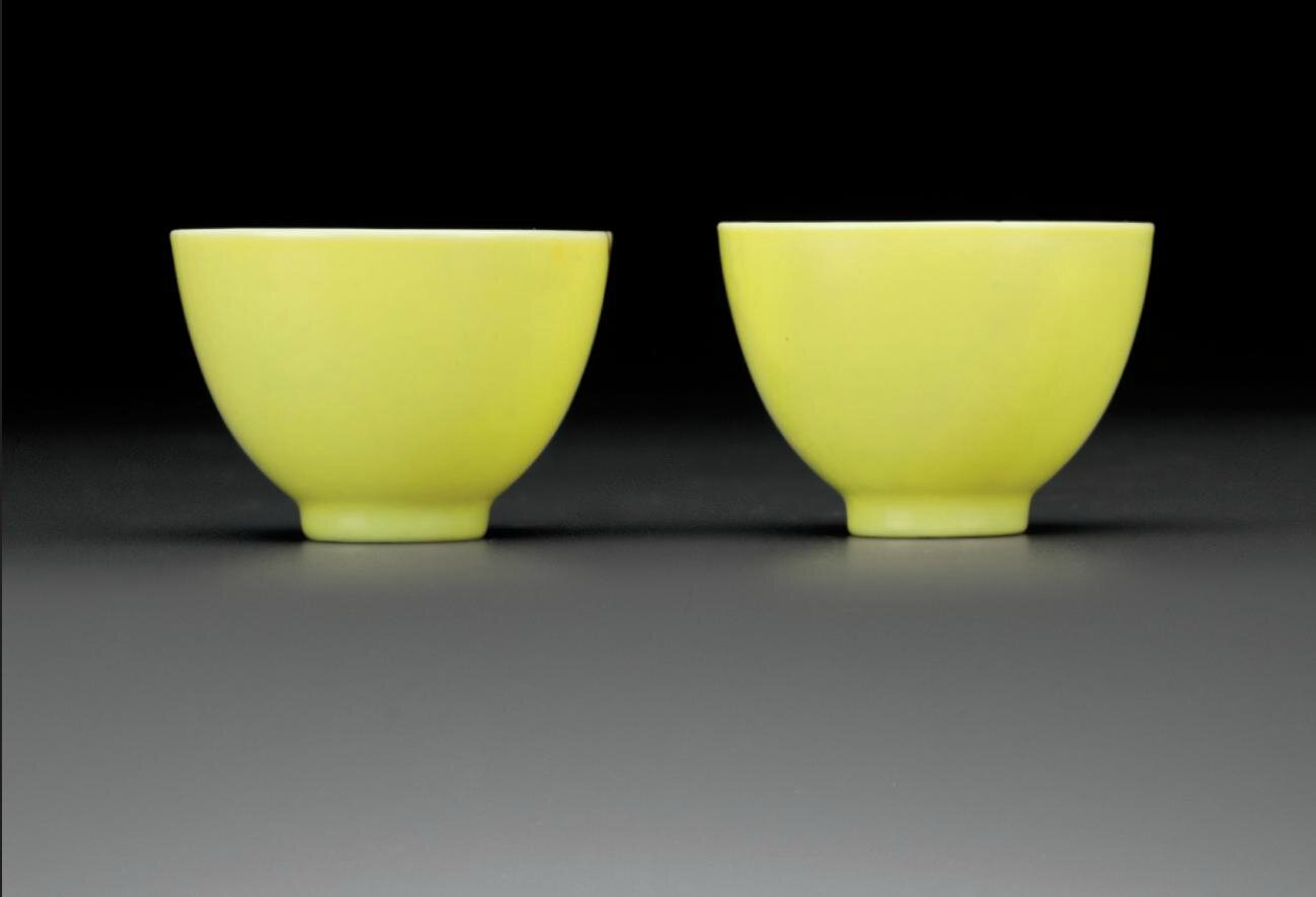 A rare pair of small lemon-yellow-enameled wine cups, Yongzheng six-character marks in underglaze-blue within circles and of the