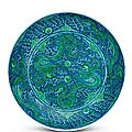 A rare large underglaze-blue ground green-enamelled 'dragon' dish, Kangxi six-character mark in underglaze blue within a double circle and of the period (1662-1722)