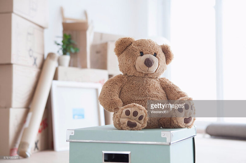 teddy-bear-sitting-on-box-in-front-of-piled-cardboard-boxes-picture-id578189381
