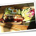 Sandwich campagnard de saucisse grillée avec salade, endive carmine et chips de lard