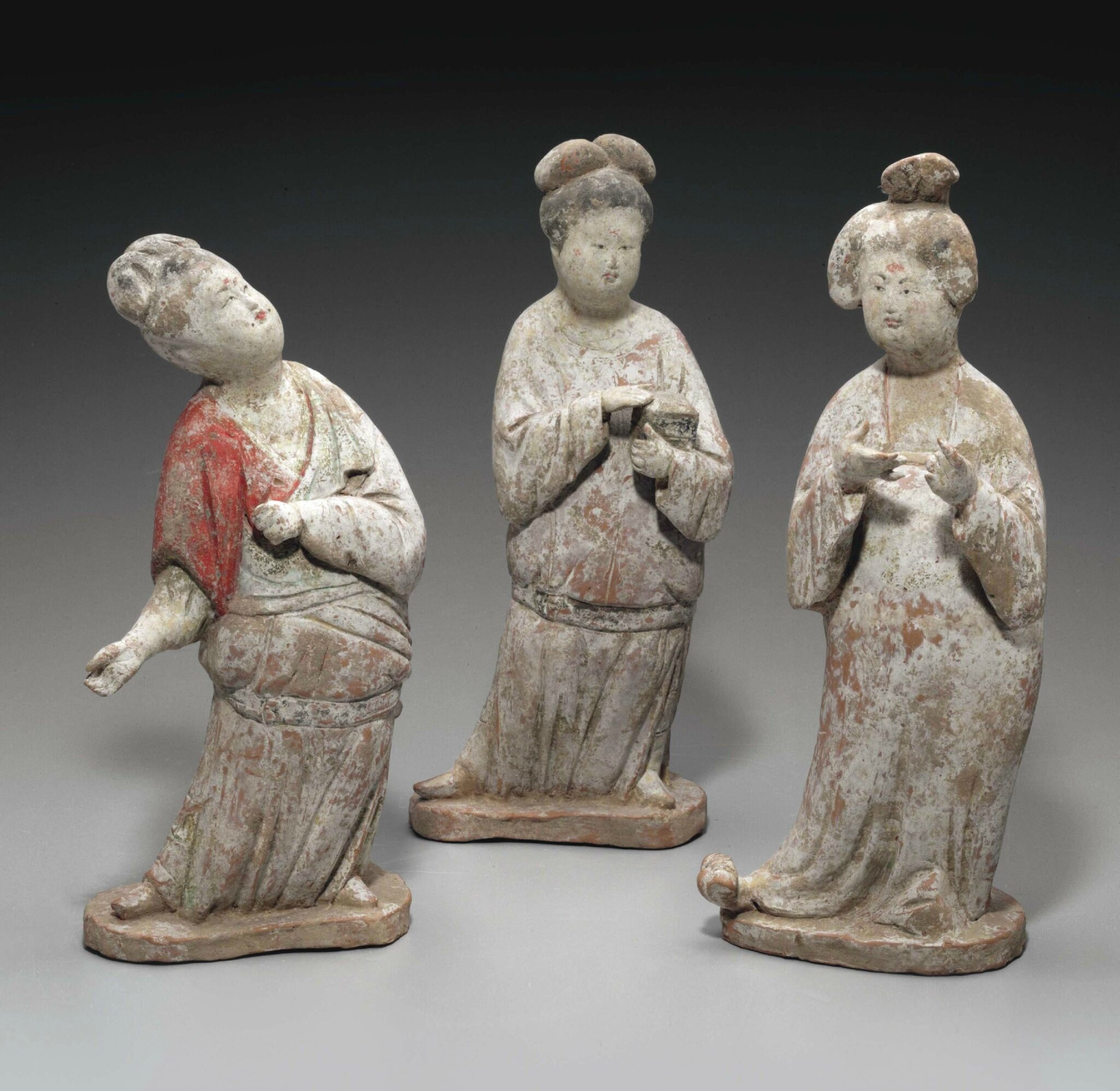 An unusual group of three painted pottery figures of court ladies, Tang dynasty (AD 618-907)
