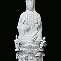 A large blanc de chine porcelain guanyin sitting on a cloud with dragons, china, qing dynasty, beginning 20th century