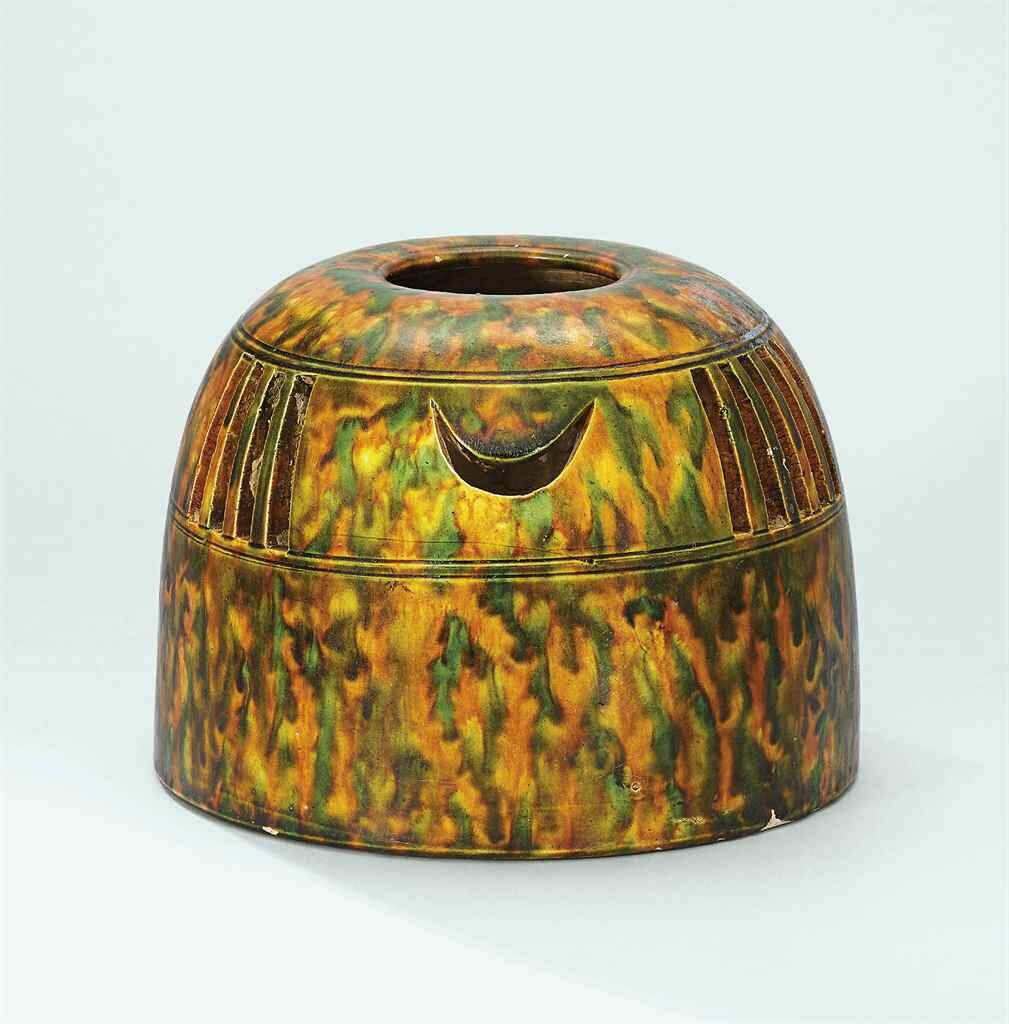 A sancai-glazed hand warmer, Tang dynasty (618-907)