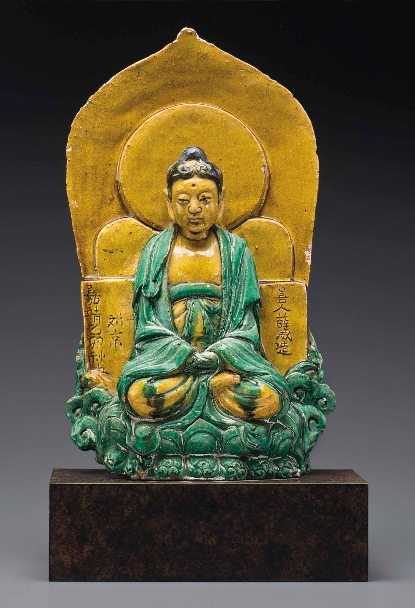 A datedsancai-glazed stoneware figure of Buddha, dated to mid-autumn of theyimaoyear of Jiajing, corresponding to 1555, and of the period
