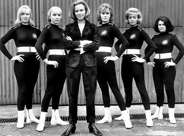 Honor Blackman as Pussy with her female pilots lined up behind her