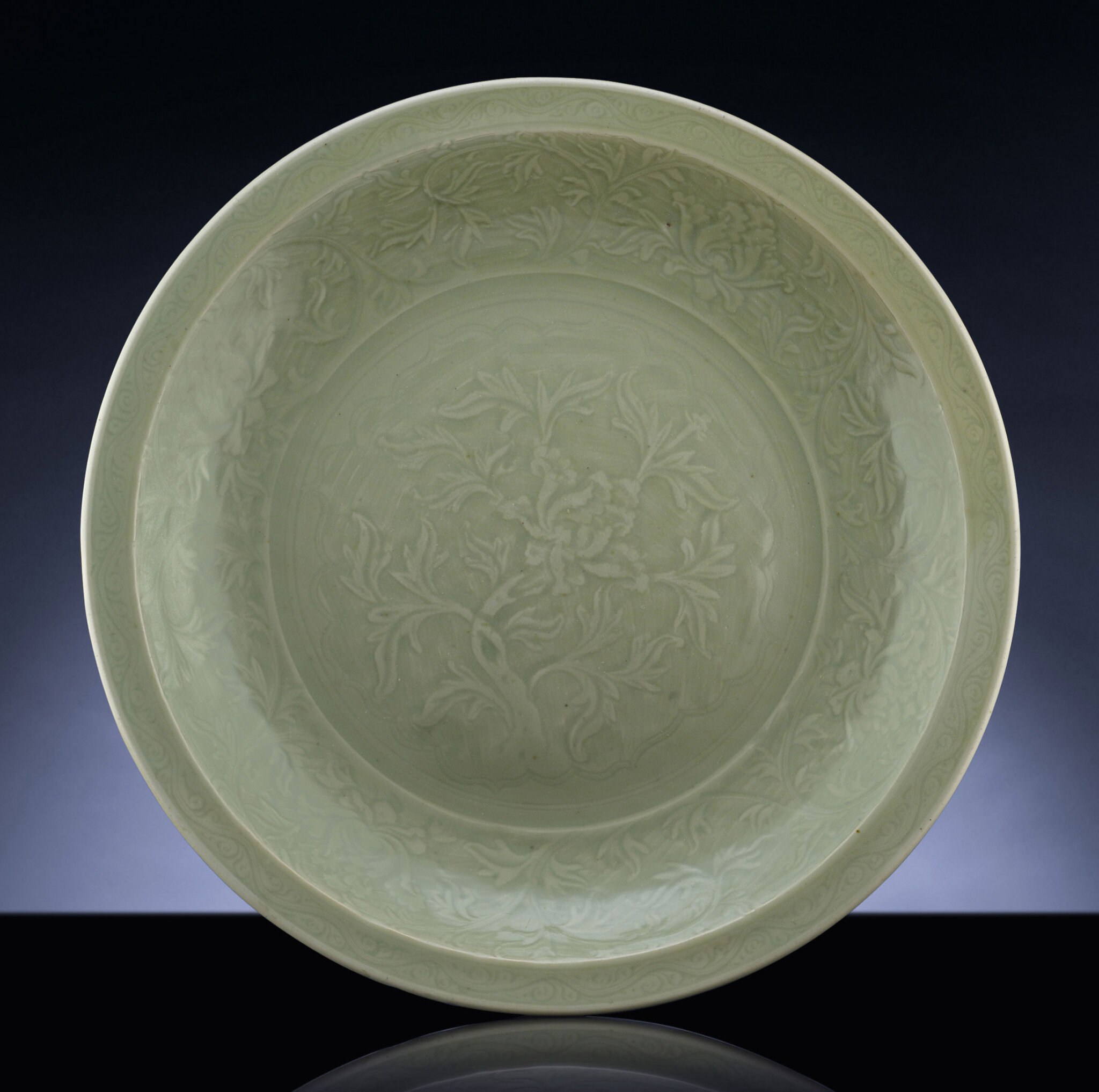 A rare early Ming massive carved Longquan celadon charger, Ming Dynasty, 14th-15th century