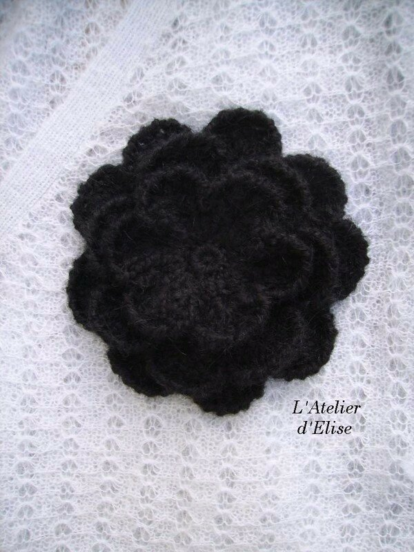 91. Broche-fleur en laine mohair noire.