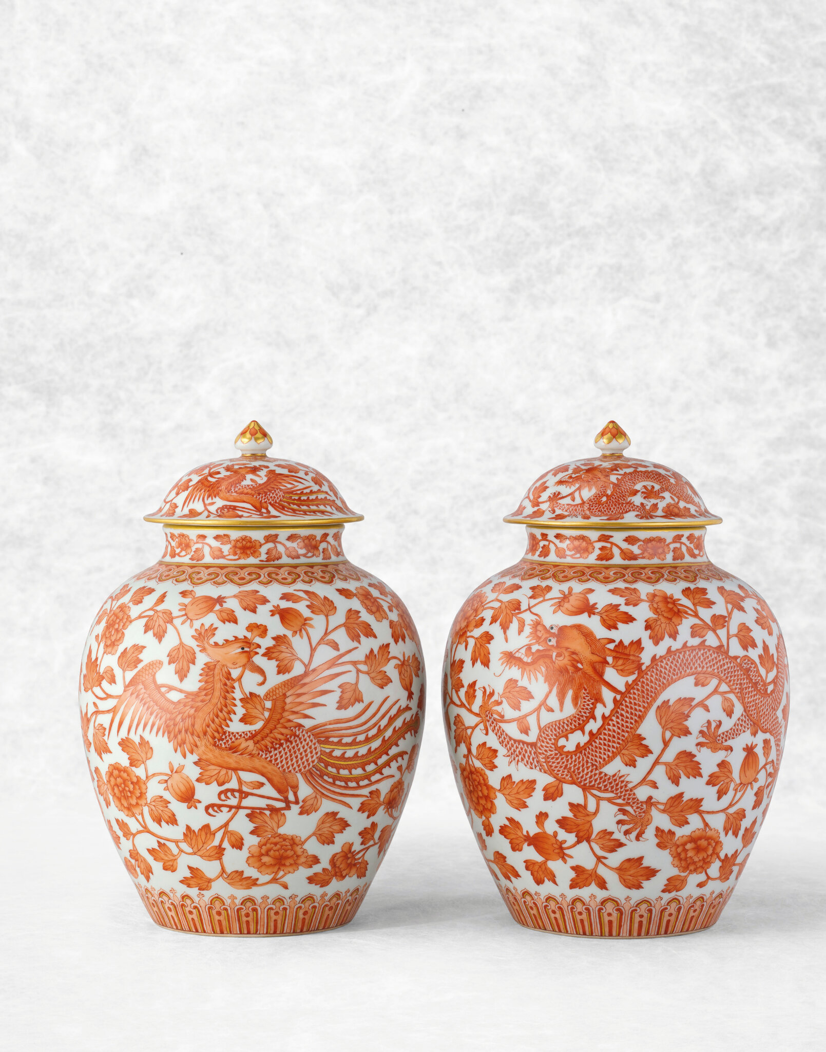 A pair of rare iron-red decorated 'dragon and phoenix' jars and covers, with Daoguang iron-red six-character seal marks and of the period (1821-1850)
