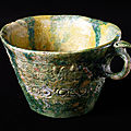 Earthenware cup with molded or stamped decoration and a yellow and green glaze, iraq or syria, 8th-9th century